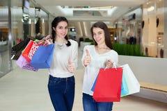 在购物中心的两逗人喜爱的女孩步行与礼物请求,显示翘拇指 图库摄影