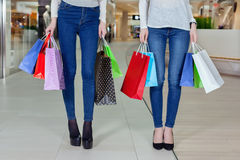 在购物中心的两逗人喜爱的女孩步行与礼物请求 关闭仅腿 库存图片