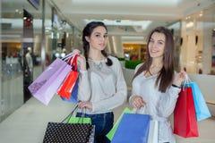在购物中心的两逗人喜爱的女孩步行与礼物请求 免版税库存图片