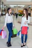 在购物中心的两逗人喜爱的女孩步行与礼物请求 库存照片