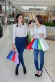 在购物中心的两逗人喜爱的女孩步行与礼物请求 免版税库存照片