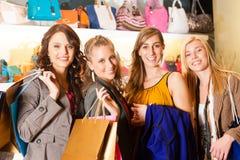 在购物中心的四个女性朋友购物袋 库存照片
