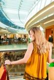 在购物中心的少妇购物与袋子 库存照片