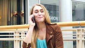 在购物中心的白肤金发的谈的电话坐长凳 影视素材