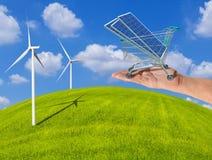 在购物台车推车的Photovoltaics太阳电池板在有引起电发电站的风轮机的妇女手上在meado 免版税图库摄影