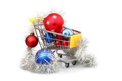 在购物台车里面的圣诞节中看不中用的物品 免版税库存照片