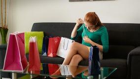 在购物的尝试时尚项链以后的拉提纳女孩在沙发 免版税图库摄影