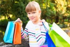 在购物以后的小女孩在公园 库存照片