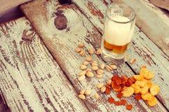 在玻璃、油煎方型小面包片和开心果的啤酒 啤酒和啤酒快餐 免版税库存照片