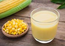 在玻璃、仁玉米在板材和新鲜的玉米的玉米牛奶 免版税库存图片