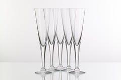 在玻璃书桌上的五块香槟玻璃 免版税库存照片