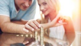 在玻璃书桌上的年轻夫妇大厦金钱专栏 免版税库存图片