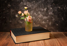 在玻璃和书的花 库存图片