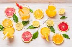 在玻璃和切片的柑橘汁桔子、葡萄柚和柠檬 免版税库存照片