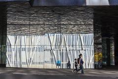 在玻璃和大厦反映的两个人 免版税库存图片