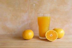 在玻璃和新鲜水果的橙汁在桌上 免版税图库摄影