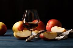 在玻璃和红色苹果的新近地被紧压的苹果汁与叶子 免版税库存照片