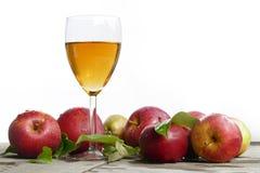 在玻璃和红色苹果的苹果汁与在老木头, w的叶子 库存照片