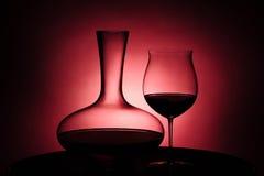 在玻璃和蒸馏瓶的红葡萄酒 免版税库存图片