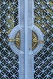 在玻璃和蓝色金属装饰门的金黄葡萄酒门把手在保加利亚城堡 免版税图库摄影