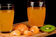 在玻璃和被剥皮的蜜桔特写镜头的汁液 库存图片