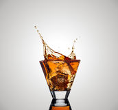 在玻璃外面的威士忌酒飞溅在白色背景 免版税库存图片
