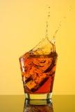 在玻璃外面的威士忌酒飞溅在黄色背景 免版税图库摄影
