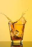 在玻璃外面的威士忌酒飞溅在黄色背景 库存图片