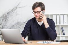 在玻璃工作的年轻商人在计算机上 免版税库存图片