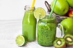 在玻璃杯子和果汁的绿色菜圆滑的人在有秸杆的,篮子用苹果,石灰,猕猴桃瓶 免版税库存照片