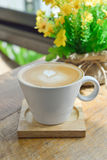 在玻璃杯子杯子的热的拿铁咖啡在木桌上 库存图片