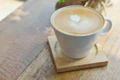 在玻璃杯子杯子的热的拿铁咖啡在木桌上 库存照片