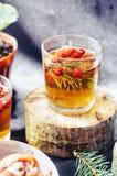 在玻璃杯子的新近地酿造的茶在蓝色背景 橙色热的饮料,选择聚焦 与红色berri酊的新鲜的清凉茶  图库摄影