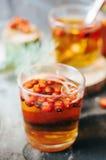 在玻璃杯子的新近地酿造的茶在蓝色背景 橙色热的饮料,选择聚焦 与红色berri酊的新鲜的清凉茶  免版税库存图片