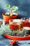 在玻璃杯子的新近地酿造的茶在蓝色背景 橙色热的饮料,选择聚焦 与红色berri酊的新鲜的清凉茶  库存图片