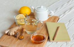 在玻璃杯子的清凉茶有春黄菊、姜黄和蜂蜜花的在一个木板 免版税图库摄影