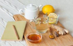在玻璃杯子的清凉茶有春黄菊、姜黄和蜂蜜花的在一个木板 库存图片