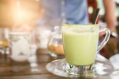 在玻璃杯子的热的绿茶牛奶 免版税库存照片