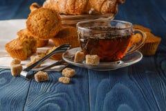 在玻璃杯子,新鲜的新月形面包,木的葡萄酒的锡兰红茶 免版税库存照片