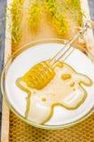 在玻璃板的新鲜的强奸蜂蜜有在蜂窝的浸染工的 库存图片
