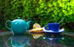在玻璃桌上每蓝色杯子用柠檬 免版税库存图片
