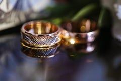 在玻璃桌上的婚戒在黑白 金子 图库摄影