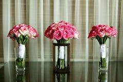 在玻璃桌上的婚礼花束 免版税库存照片