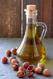 在玻璃瓶和坚果的榛子油 库存图片