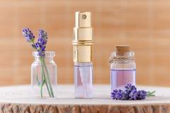 在玻璃瓶和新鲜的淡紫色的薰衣草香水在棕色背景开花为放松 库存图片