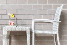在玻璃瓶和计算机的特写镜头人为五颜六色的花在与木织法椅子的木织法桌上在被弄脏的棕色砖w 免版税库存照片