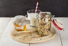 在玻璃瓶子、杯牛奶和瓶子的格兰诺拉麦片在白色wo的蜂蜜 免版税图库摄影