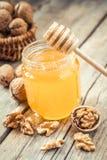 在玻璃瓶子、核桃在篮子和木浸染工的蜂蜜 库存照片