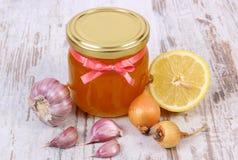 在玻璃瓶子、葱、柠檬和大蒜,健康营养和加强免疫的蜂蜜 库存照片