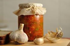 在玻璃瓶子、面包和大蒜的罐装菜 库存照片